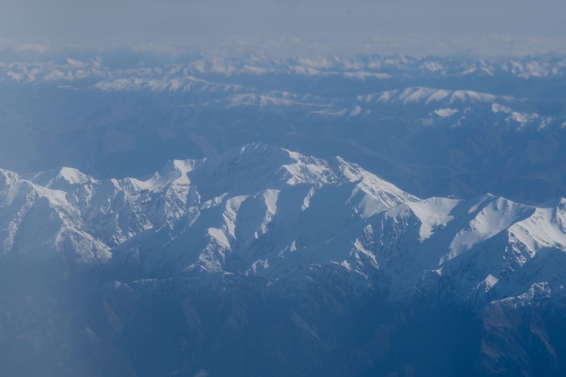 Snow topped mountains from a plane window.