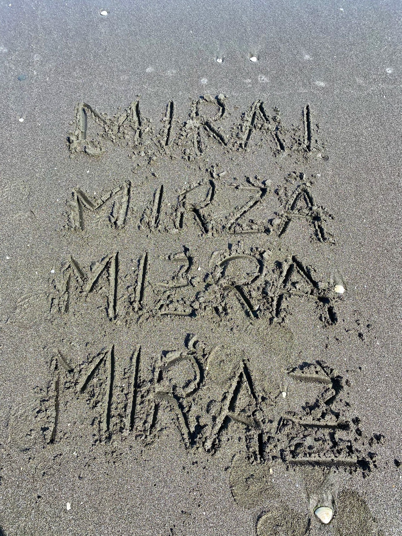 Variations of my name written in sand at the beach.