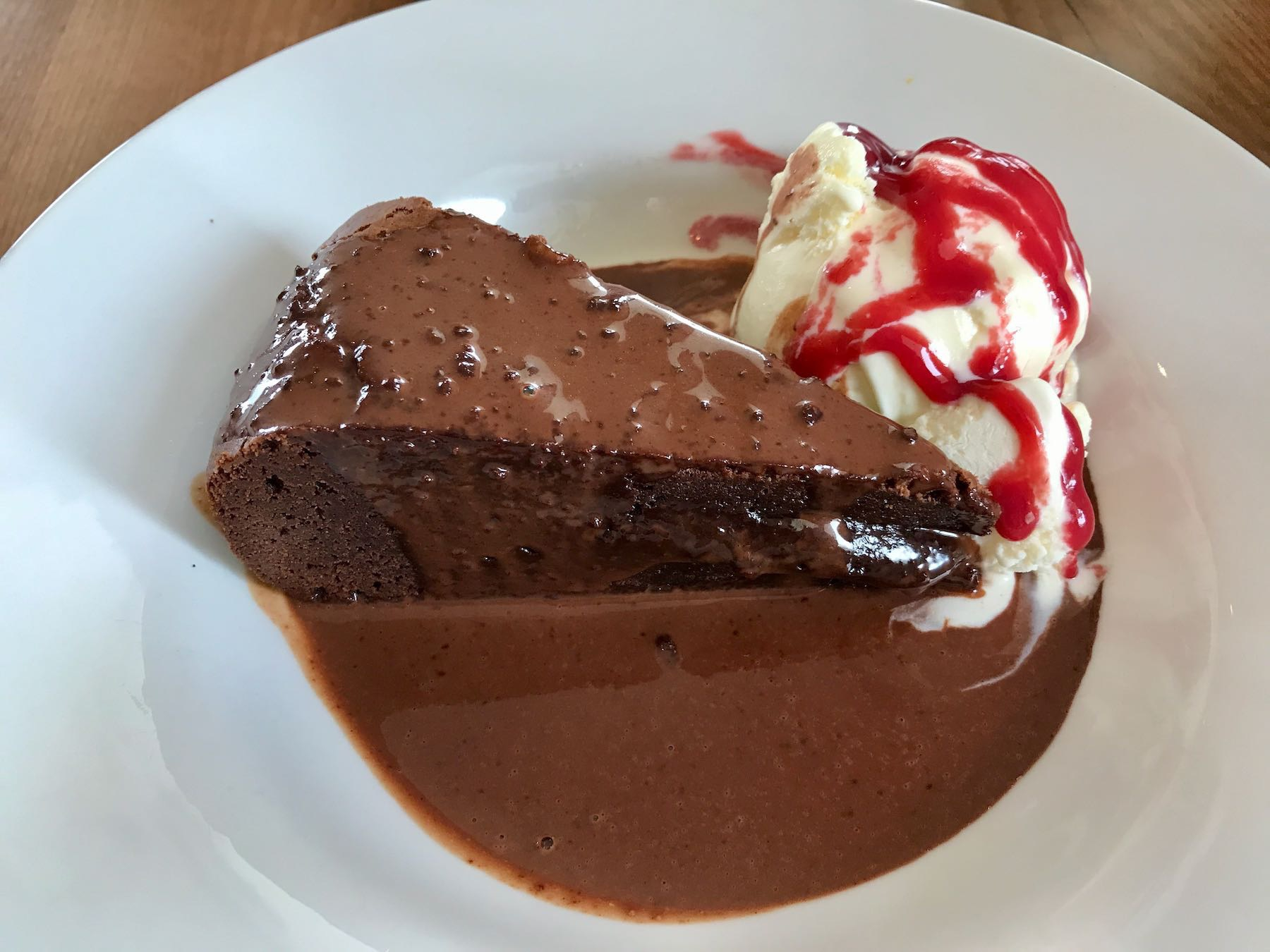 A white plate with a large slice of chocolate iced chocolate cake and a scoop of ice cream.