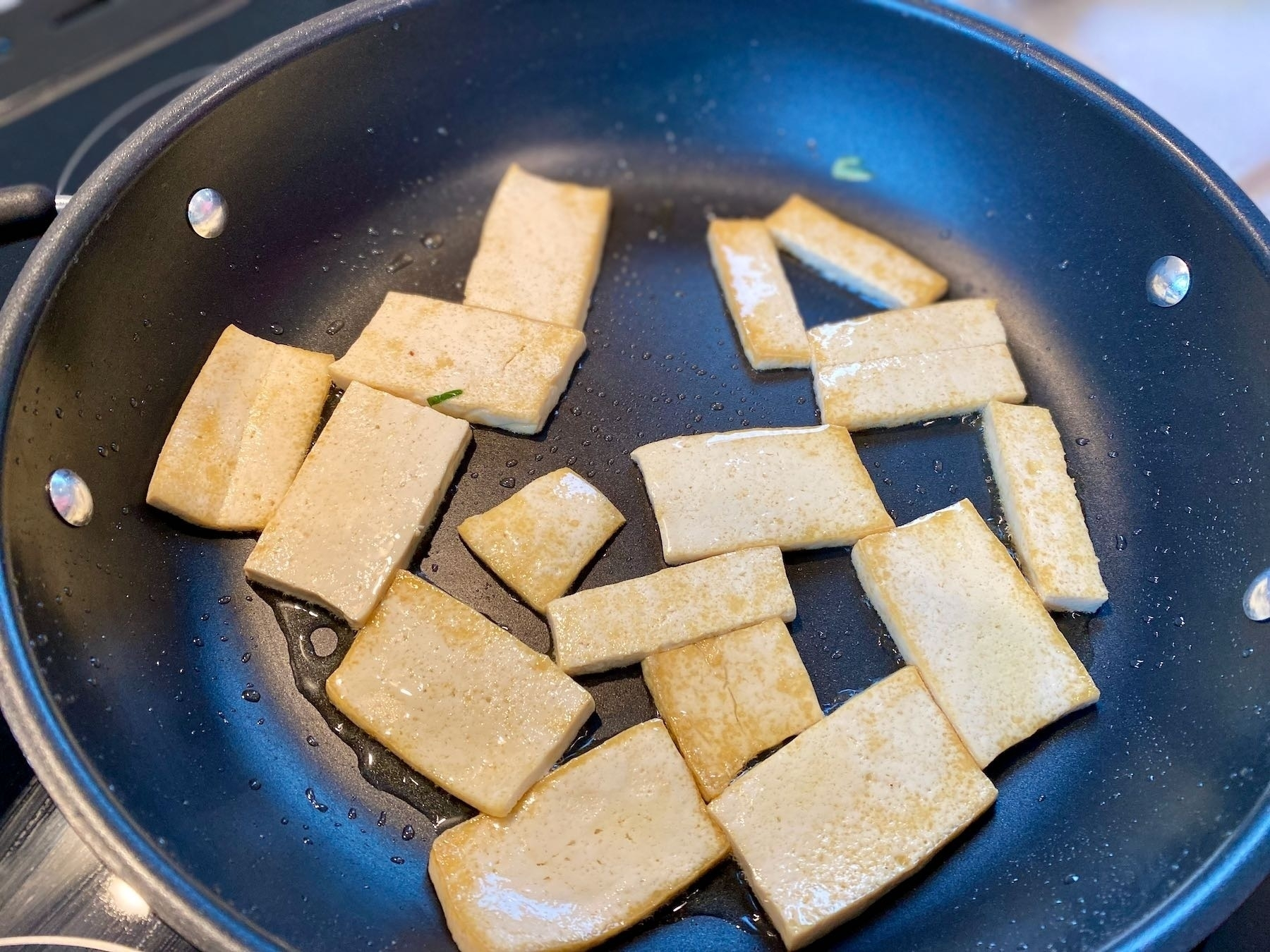 Tofu coooking in a pan.