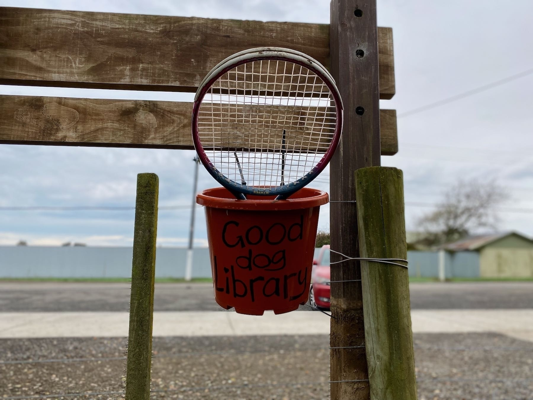 Bucket labelled Good Dog Library, with a tennis racket in it.