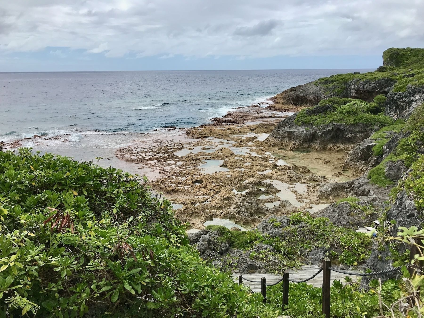 Sea, rocky reef, steps down and green vegetation.
