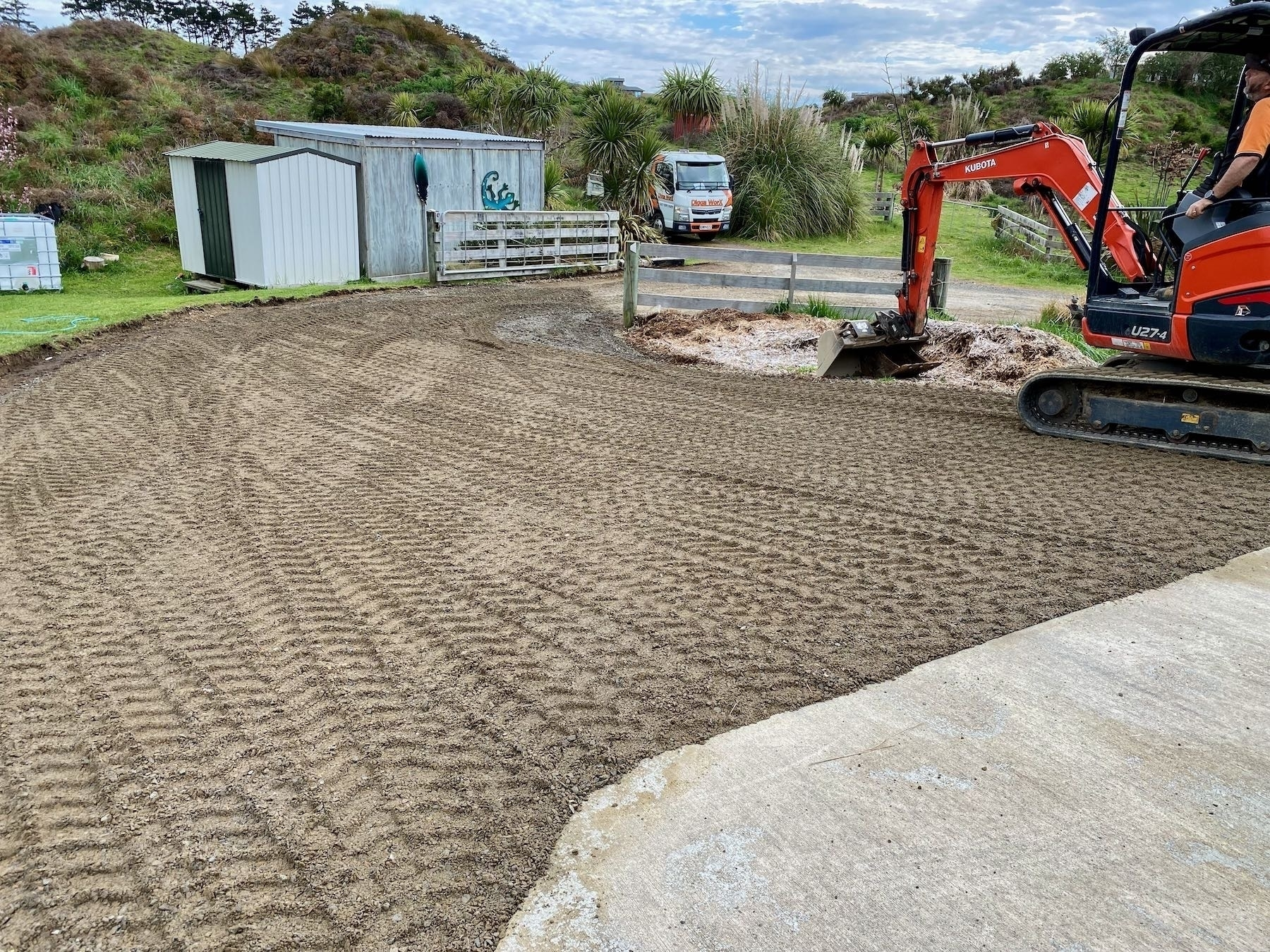 A fresh layer of shingle on the driveway, showing digger tread tracks.