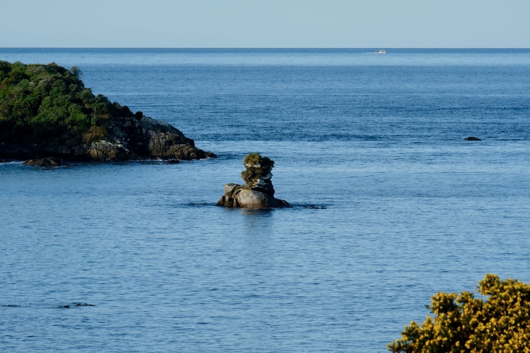 Rocky island with boat in the background.
