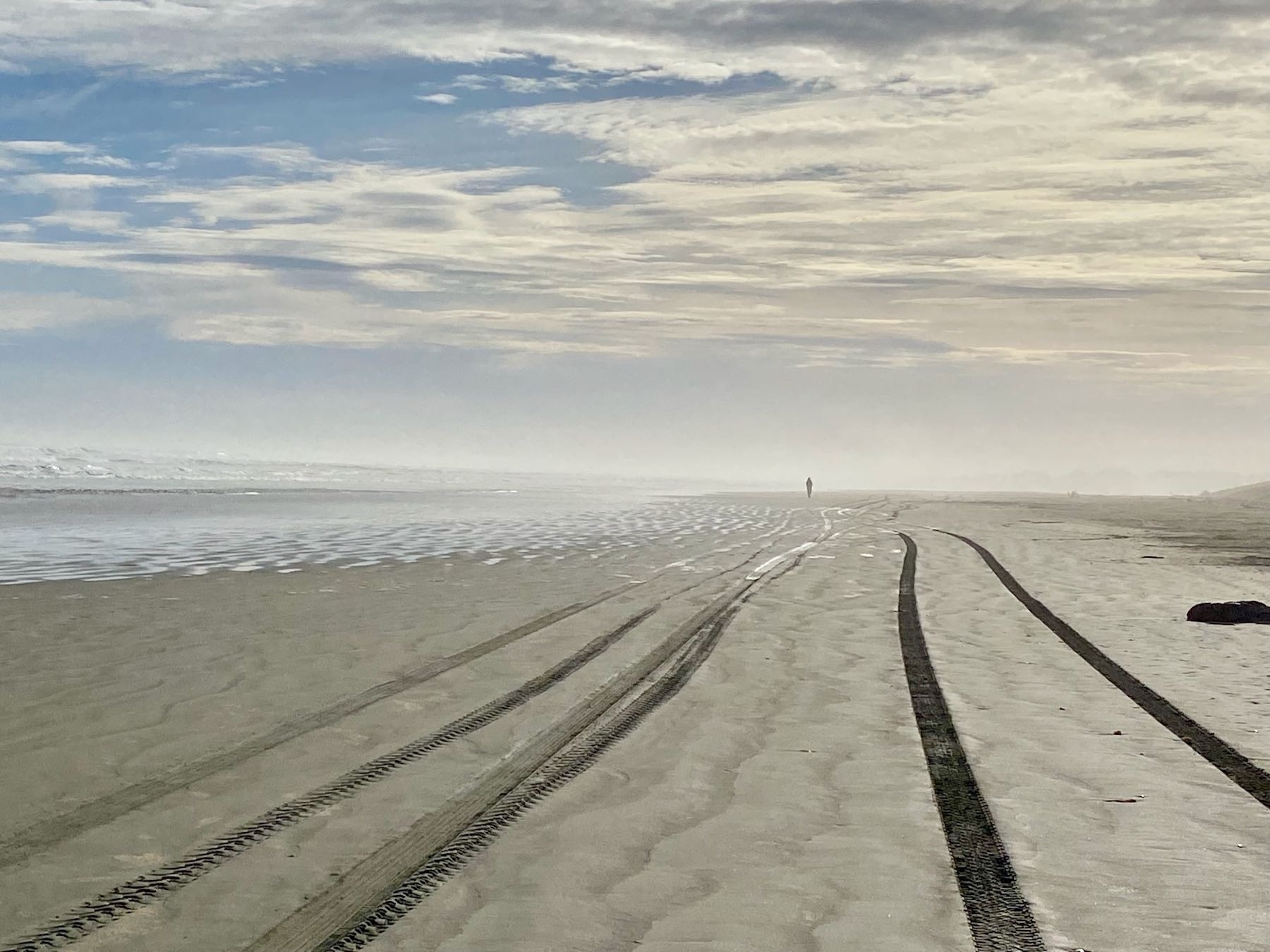 Tire tracks along the beach leading to the distance with a runner receding into the mist.