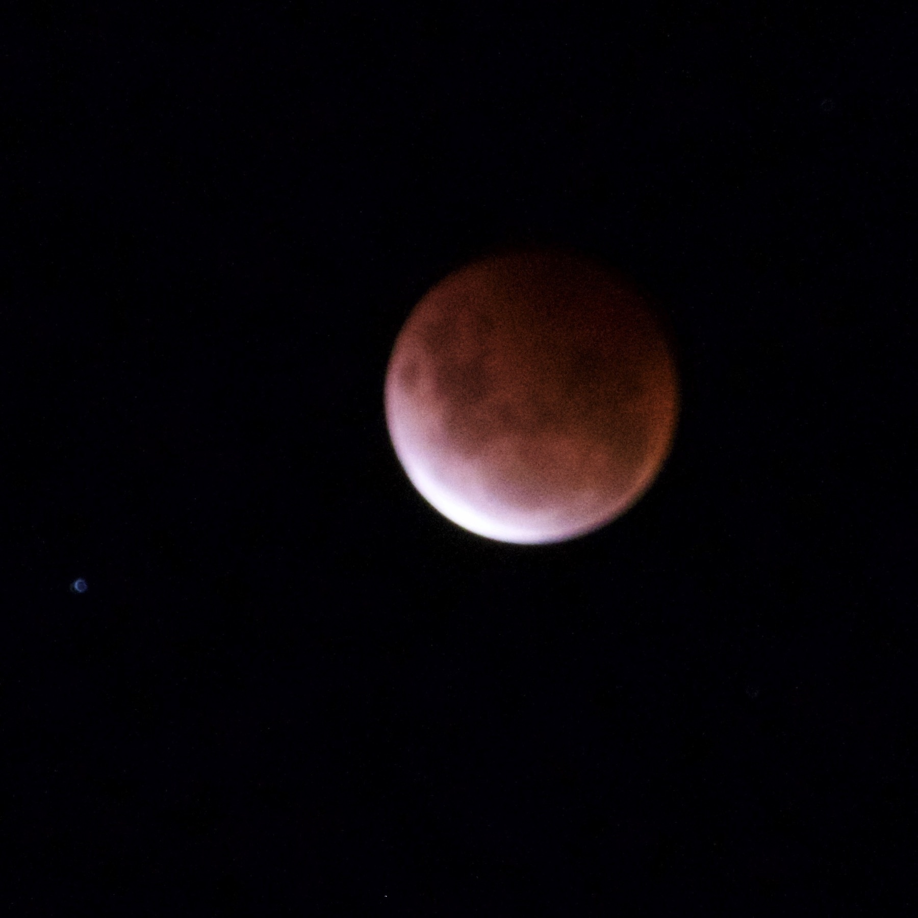 Red-tinged moon with a sliver of white at bottom left.