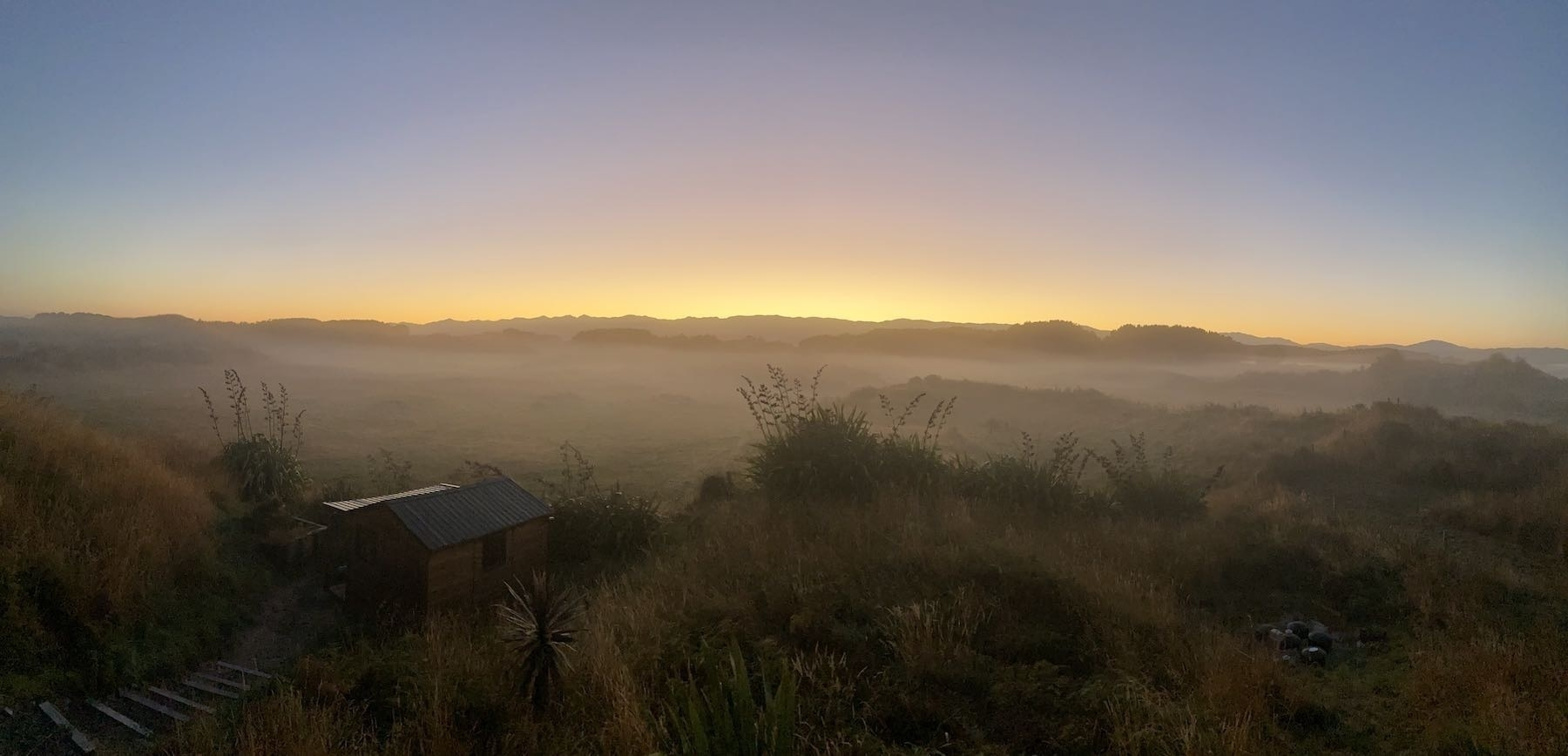 Ground fog over paddocks with golden glow behind distant hills.
