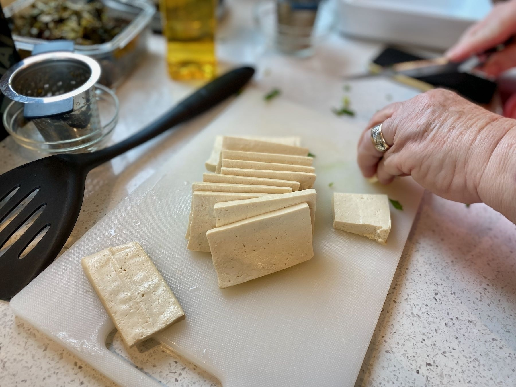 Tofu being sliced on a board.