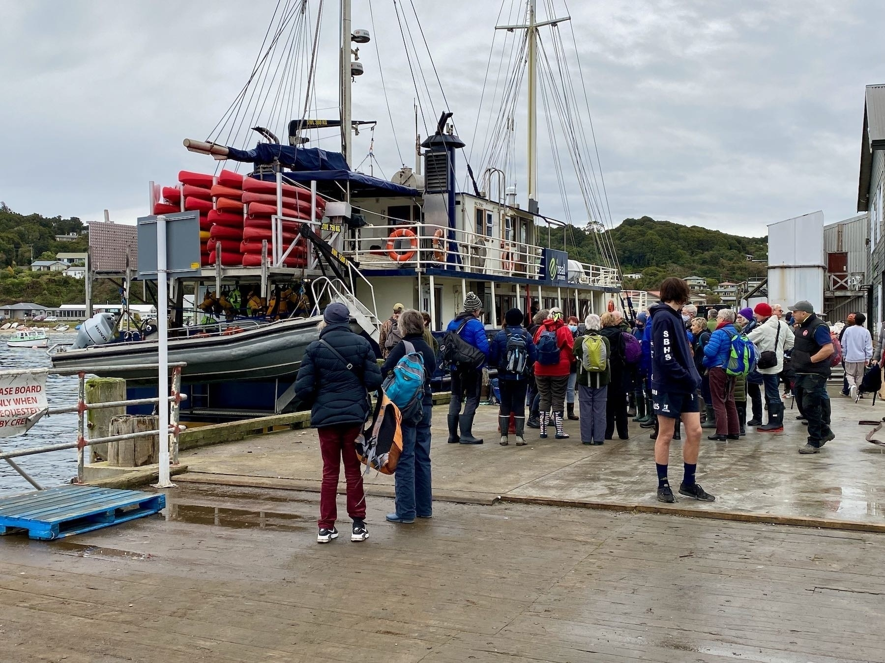 A dock with people on it with the Milford Wanderer behind them and the tender hanging from the stern.