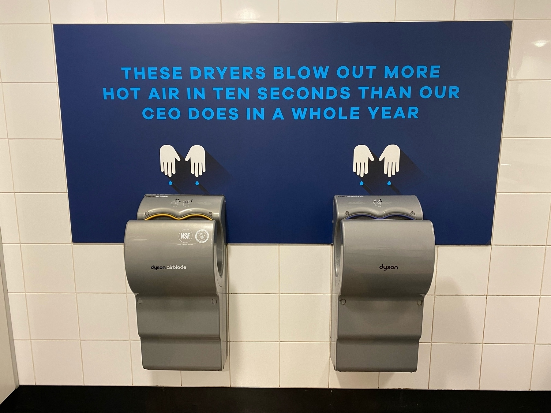 Hot air hand dryers with sign that says These dryers blow out more hot air in 10 seconds than our CEO does in a year.