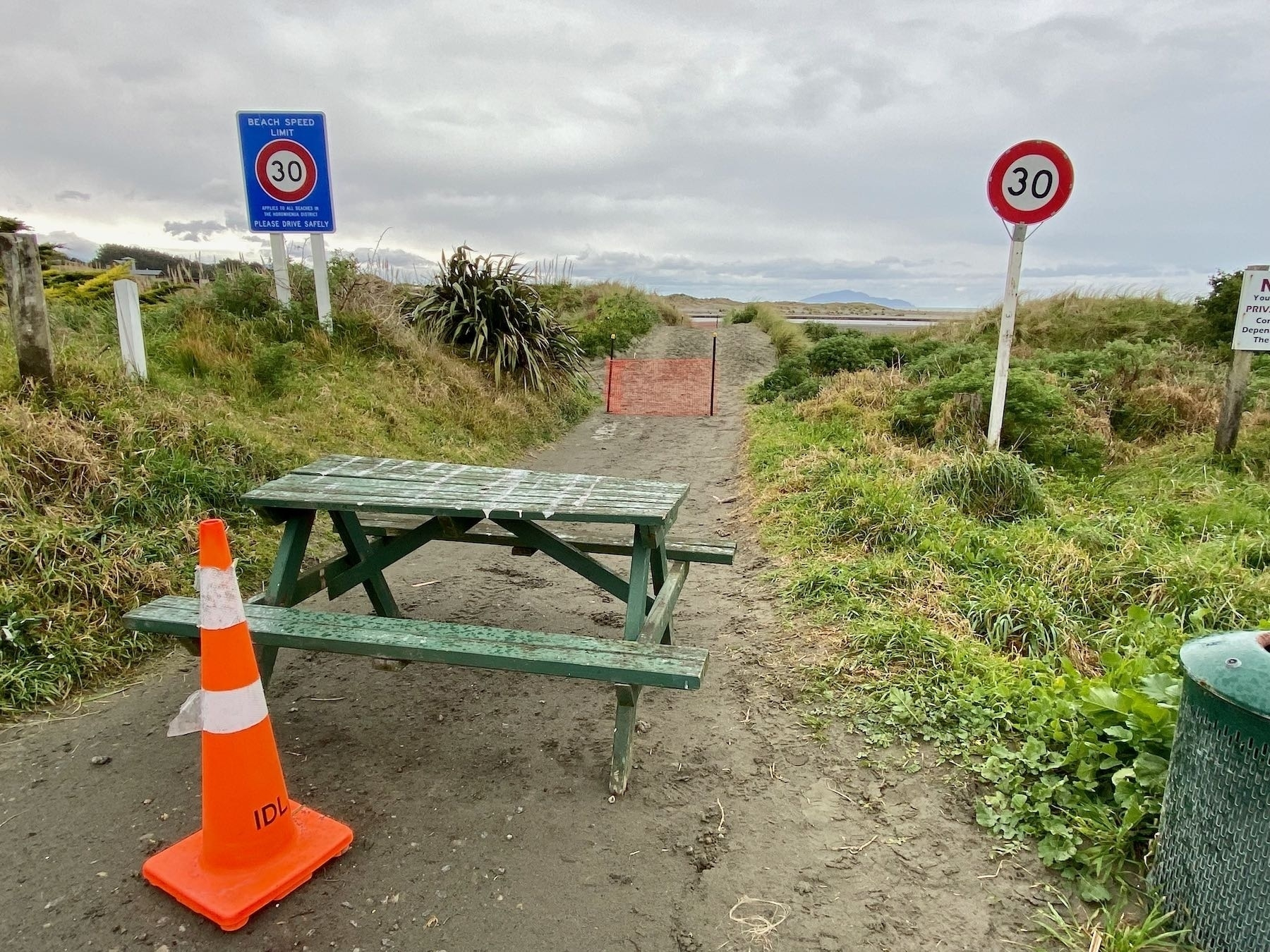 Picnic table, cone and temporary fence across the beach access road.