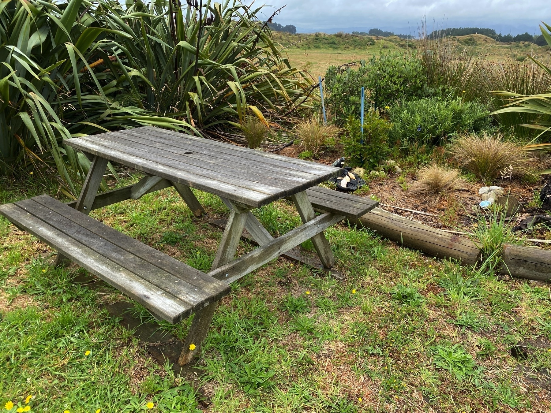 Wooden picnic table with attached bench seats.