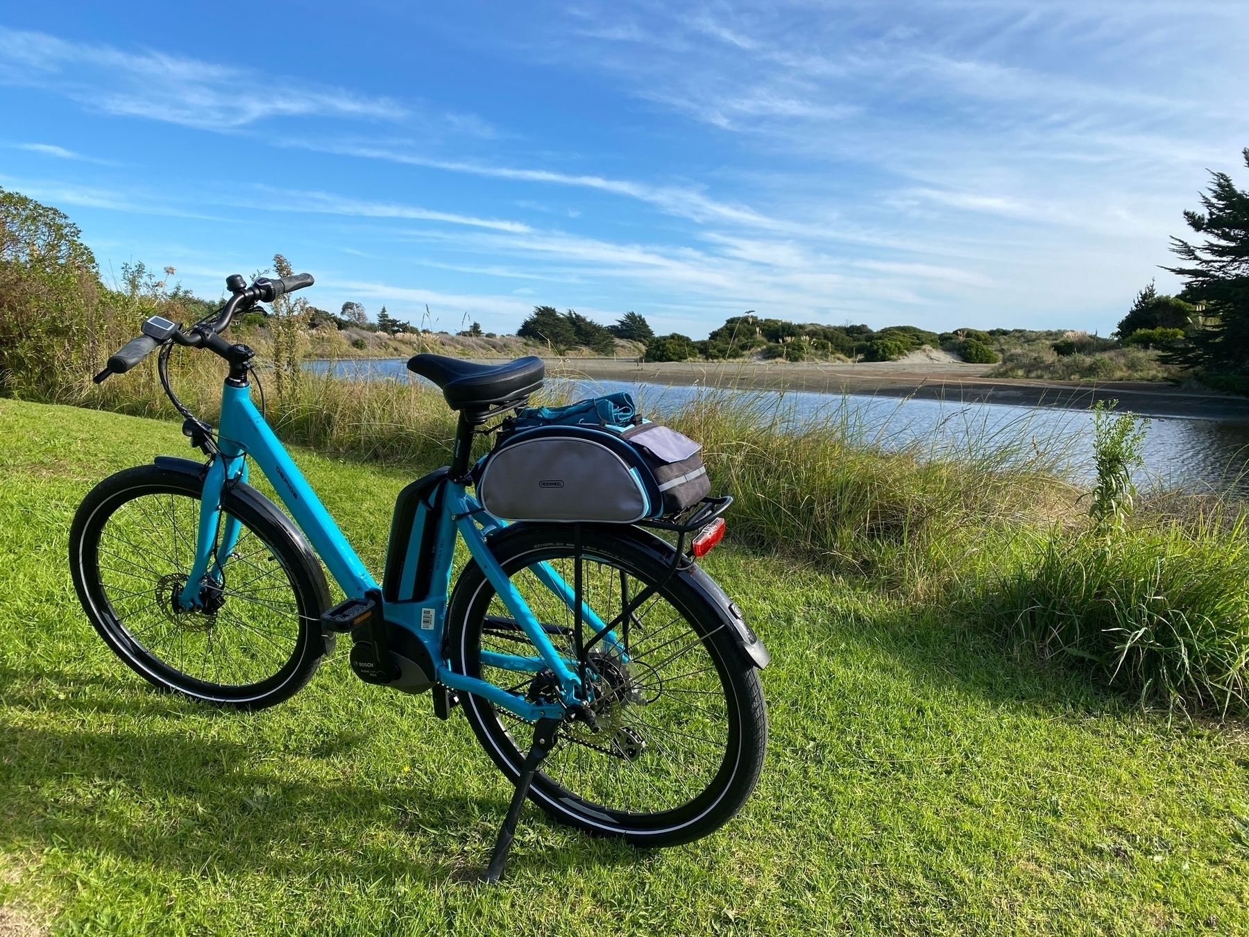 Blue bicycle beside river.