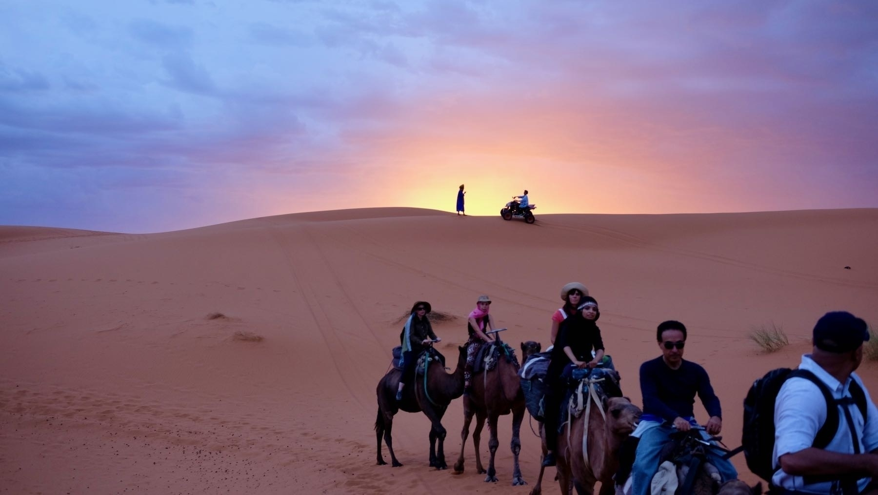 Sunrise in the desert with camel train.