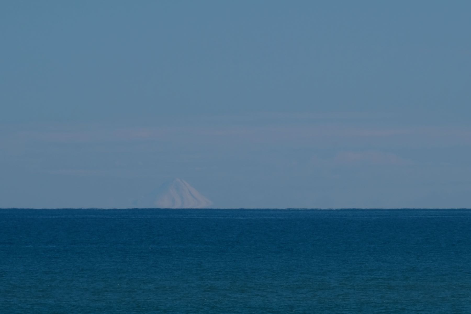White snow clad conical mountain across the sea.