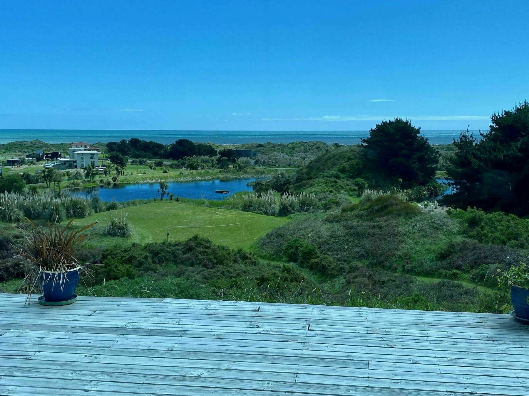 View from a hill across grassy land and dunes to the sea.