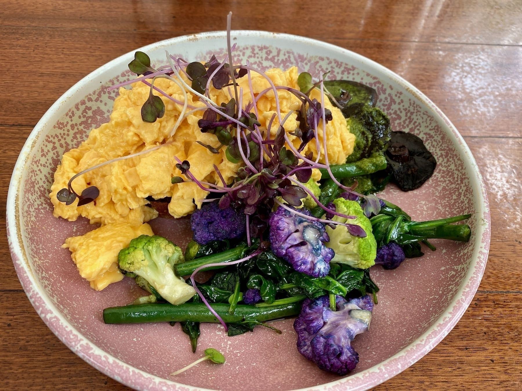 Scrambled eggs with green vegetables and mushrooms.