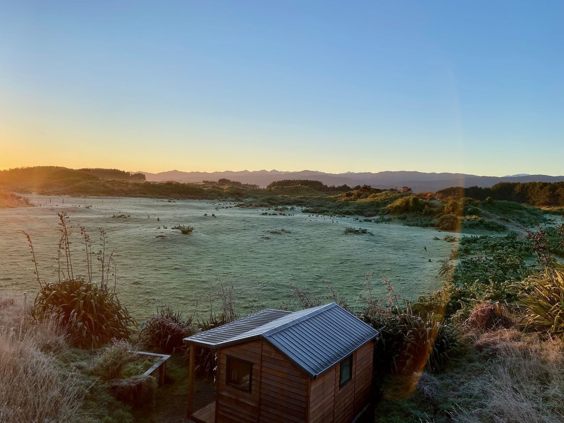 Frosty paddocks with sun just at the left edge.