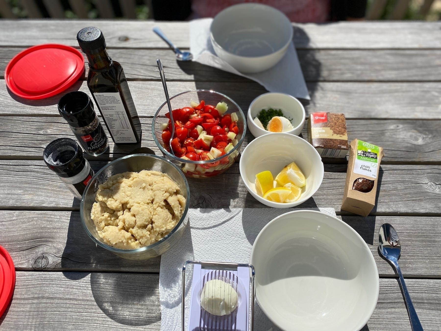 Breakfast ingredients spread on a picnic table.