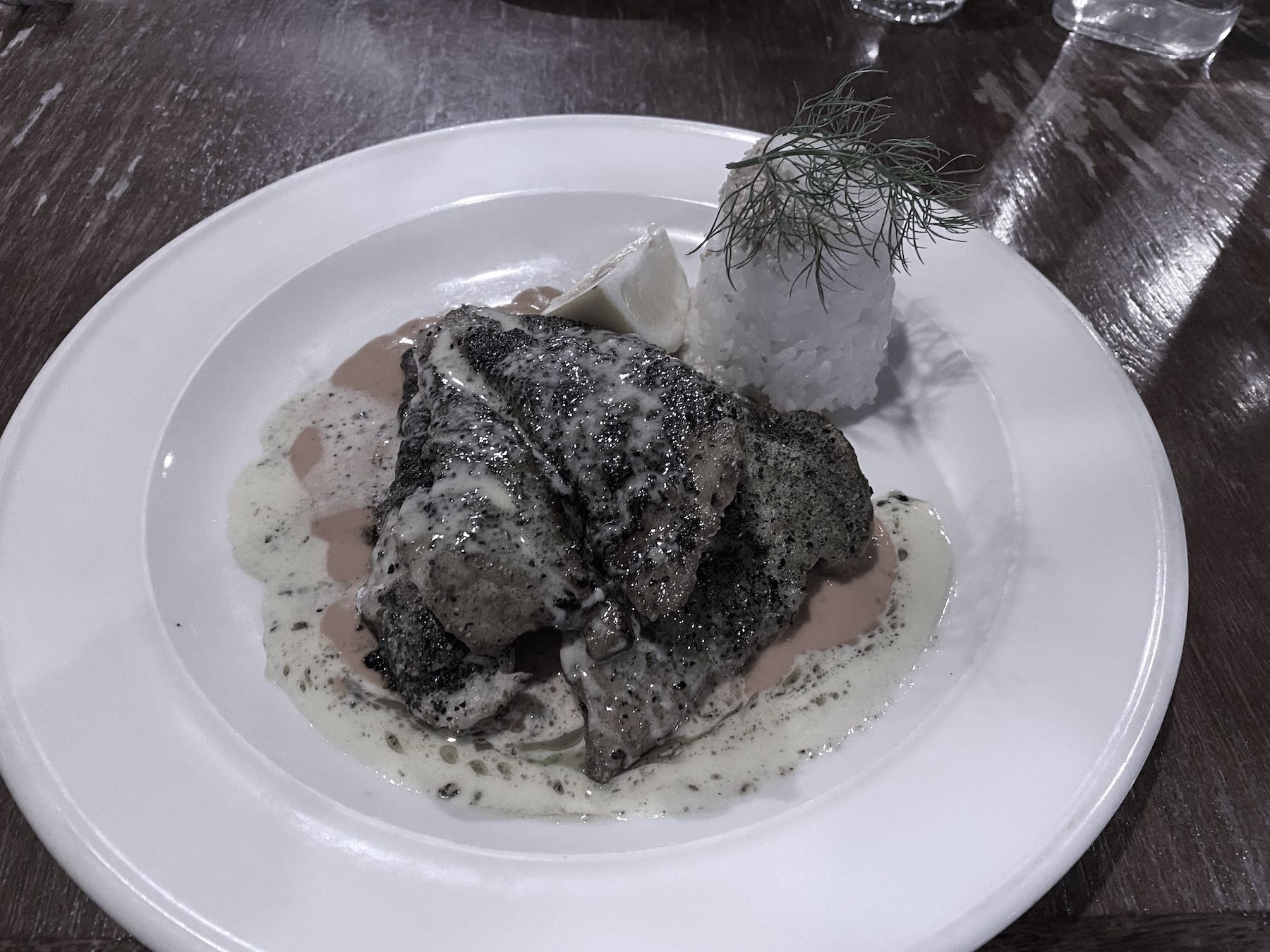 Panfried hapuka with white rice on a white plate.