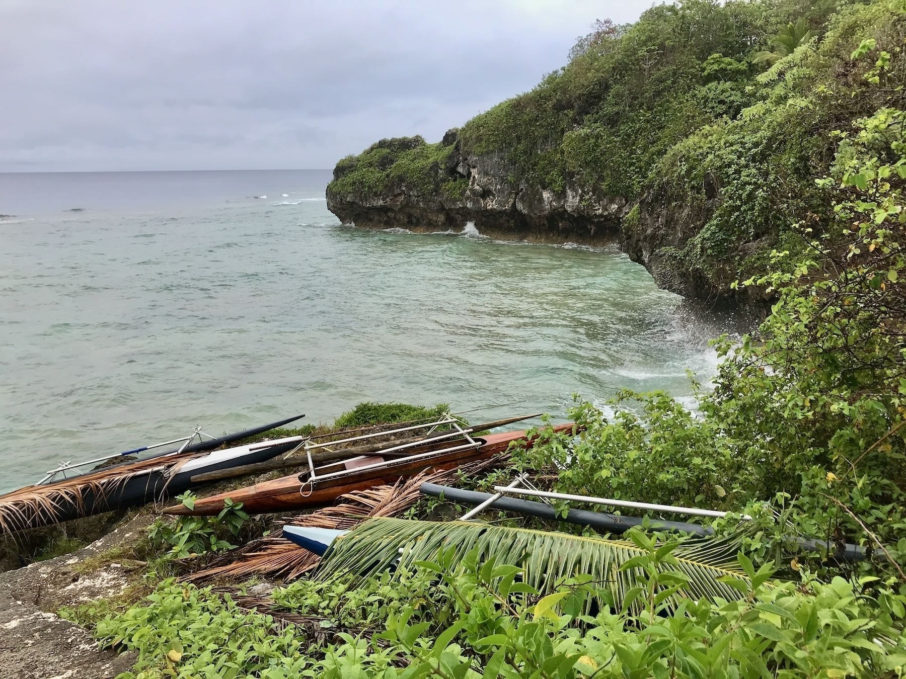 Outrigger canoes high above the water by steep rocky cliffs.